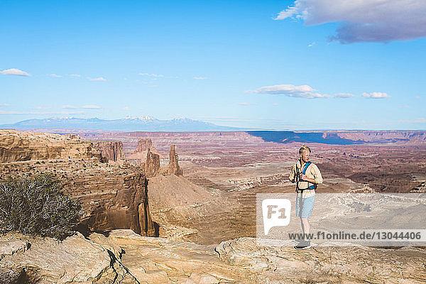 Männlicher Wanderer in voller Länge auf Berg vor blauem Himmel stehend