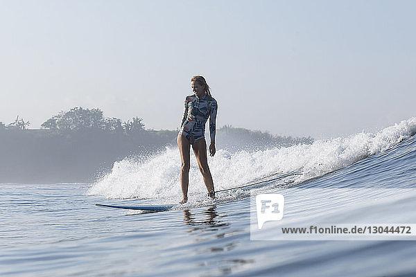 Frau surft auf dem Meer vor klarem Himmel