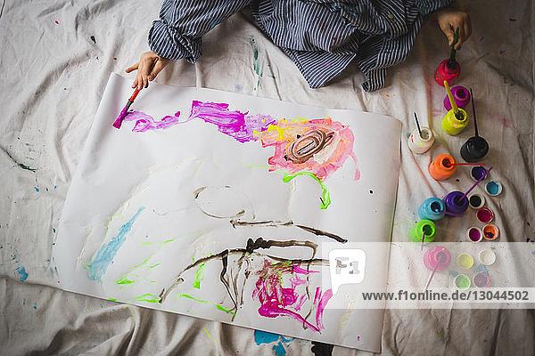 Hochwinkelansicht eines Jungen  der zu Hause auf Papier malt