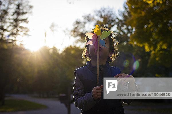 Verspielter Junge bläst Spielzeug mit einem Windrad  während er auf einem Fußweg gegen den Himmel steht