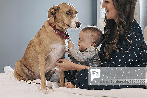 Mother and son playing dog while sitting on bed at home