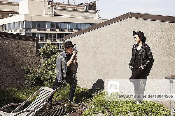 Mann fotografiert Frau durch Sofortbildkamera auf der Terrasse