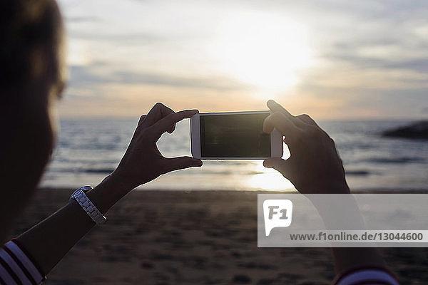 Frau fotografiert Meer  während sie bei Sonnenuntergang am Strand sitzt