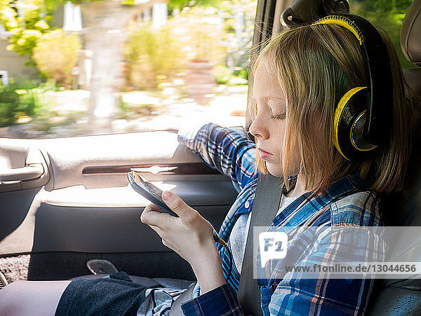 Boy looking at mobile phone while listening music in car