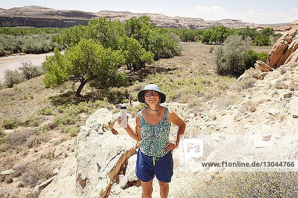 Hochwinkelporträt einer selbstbewussten Frau mit Hand auf der Hüfte auf Felsen stehend