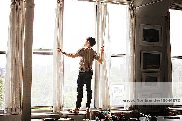 Rückansicht eines nachdenklichen Mannes  der zu Hause auf dem Fensterbrett steht