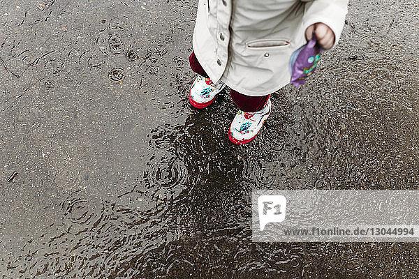 Unterer Teil eines Mädchens  das Gummistiefel trägt  während es auf einem nassen Fußweg steht