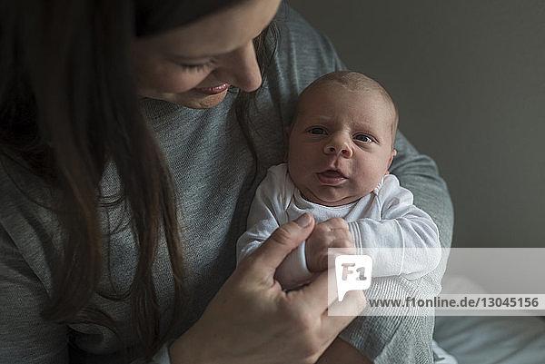 Lächelnde Mutter betrachtet süßes Neugeborenes zu Hause