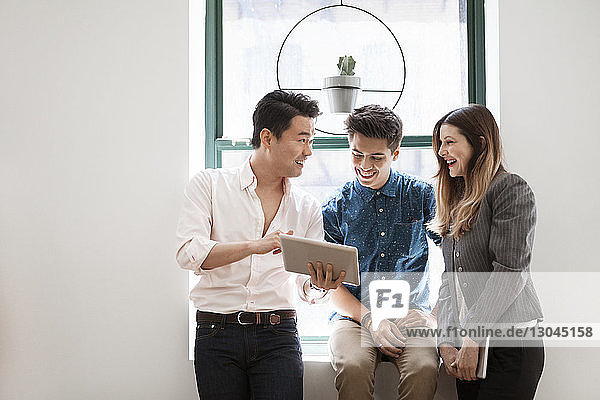 Happy businessman explaining strategy to colleagues in office