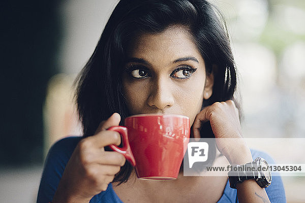 Thoughtful young woman drinking coffee at sidewalk cafe