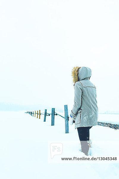 Rückansicht einer Frau,  die an einem Geländer auf einem schneebedeckten Feld steht