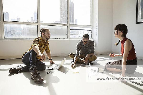 Geschäftsleute diskutieren  während sie im Kreativbüro am Boden sitzen