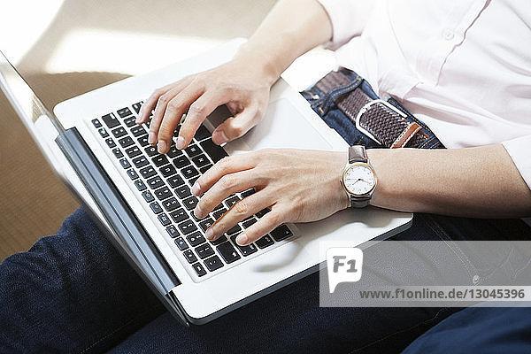 Mittelteil eines Geschäftsmannes mit Laptop im Kreativbüro Mittelteil eines Geschäftsmannes mit Laptop im Kreativbüro