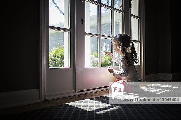 Girl writing with lipstick on door at home