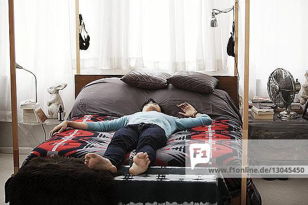 Mann liegt zu Hause auf Himmelbett