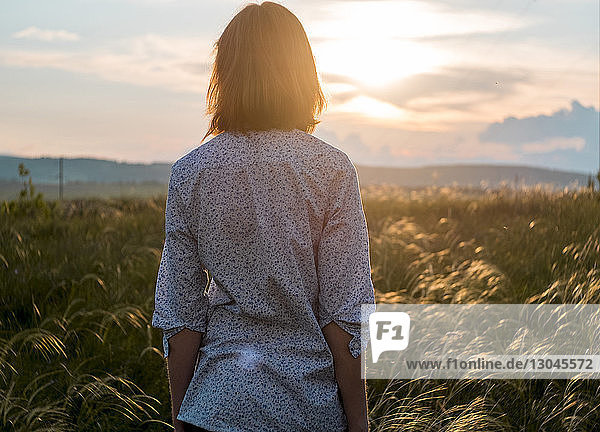 Rückansicht einer Frau  die bei Sonnenuntergang auf dem Feld gegen den Himmel steht