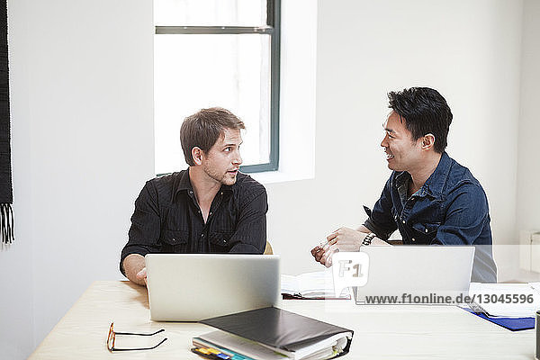 Geschäftsmann diskutiert mit männlichem Kollegen am Schreibtisch im Kreativbüro Geschäftsmann diskutiert mit männlichem Kollegen am Schreibtisch im Kreativbüro