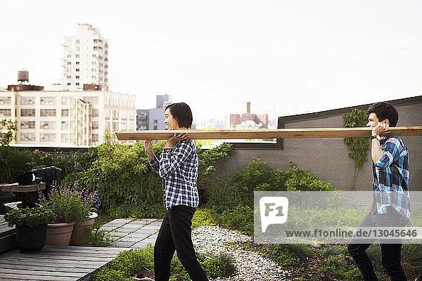 Seitenansicht eines Paares  das beim Betreten der Terrasse ein Holzbrett trägt