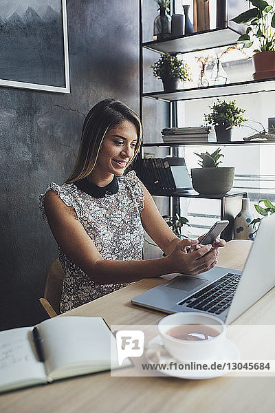 Happy businesswoman using mobile phone while sitting at table in home office