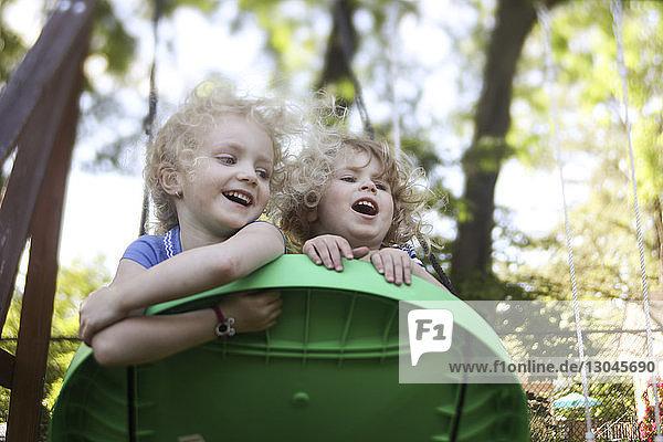 Niedrigwinkelansicht von Schwestern  die auf Außenspielgeräten auf dem Spielplatz spielen