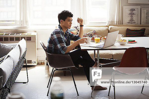 Side view of man using laptop while having breakfast at home