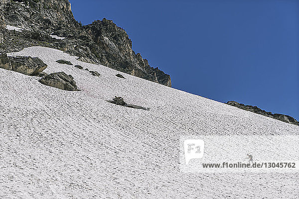 Mid distance view of man climbing snowcapped mountain against clear blue sky