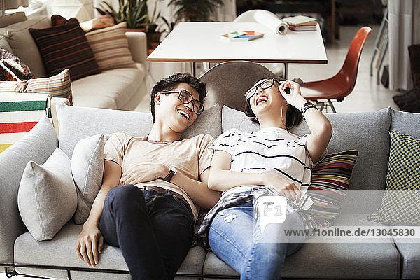 Fröhliches multiethnisches Paar unterhält sich zu Hause auf dem Sofa liegend
