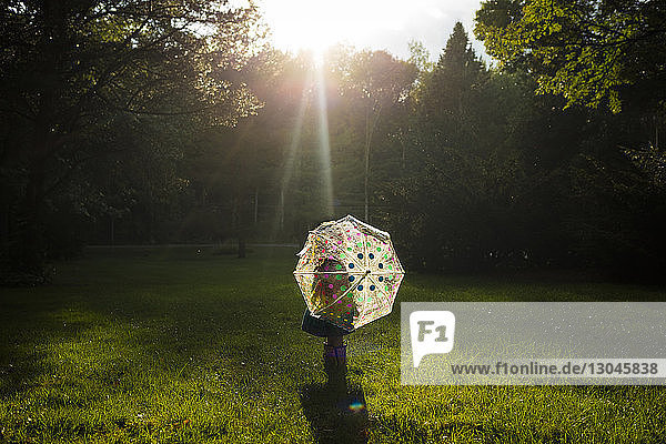 Rear view of girl carrying umbrella while standing on grassy field in park