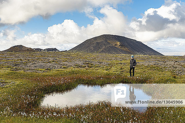 Hiker standing by pond on field against mountains and cloudy sky