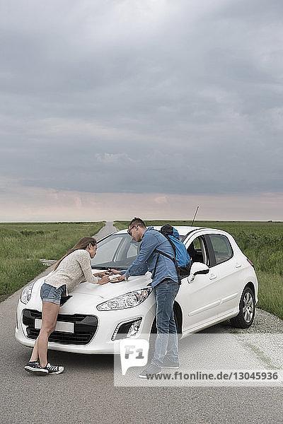 Ehepaar liest Tagebuch auf der Motorhaube eines Autos auf der Landstraße vor bewölktem Himmel