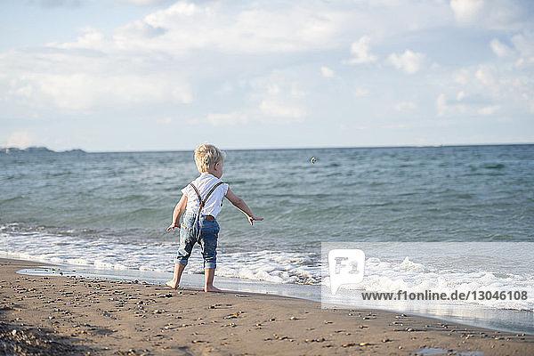 Rückansicht eines kleinen Jungen  der am Strand vor wolkenverhangenem Himmel stehend einen Stein abschöpft