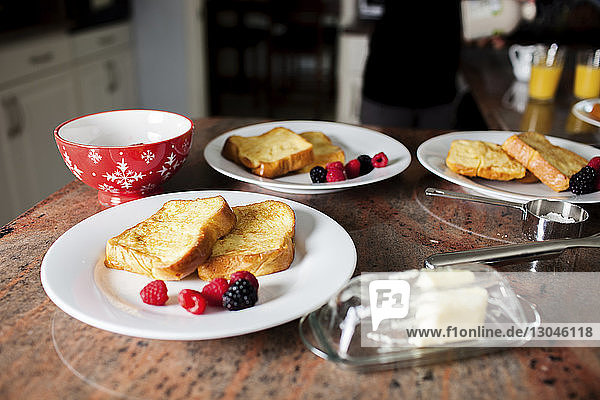 Close-up of toasted breads with berry fruits in plates on table at home
