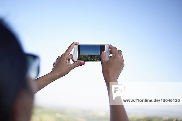 Cropped hands of woman photographing with mobile phone against clear sky