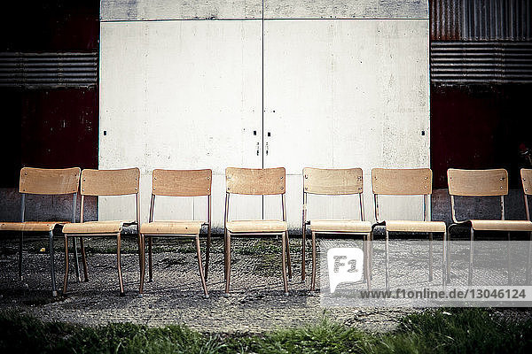Leere Stühle auf Fußweg gegen geschlossene Tür