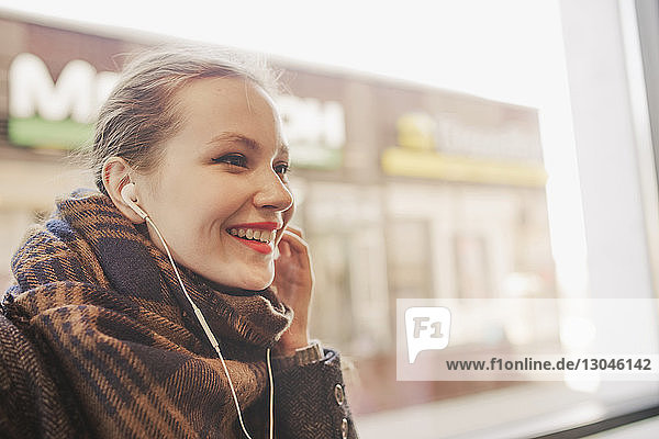 Nahaufnahme einer glücklichen Frau  die in eine Decke gehüllt Musik hört