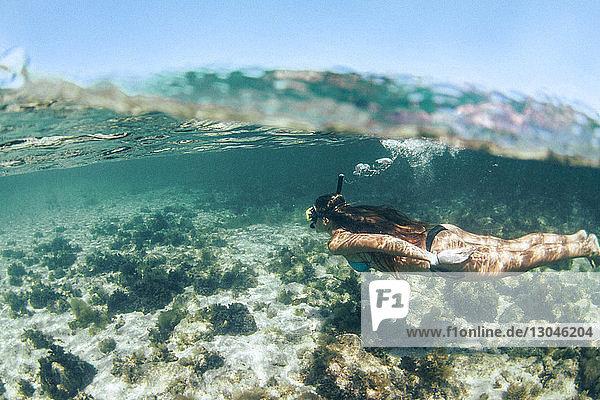 Seitenansicht einer Frau im Bikini beim Schnorcheln unter Wasser