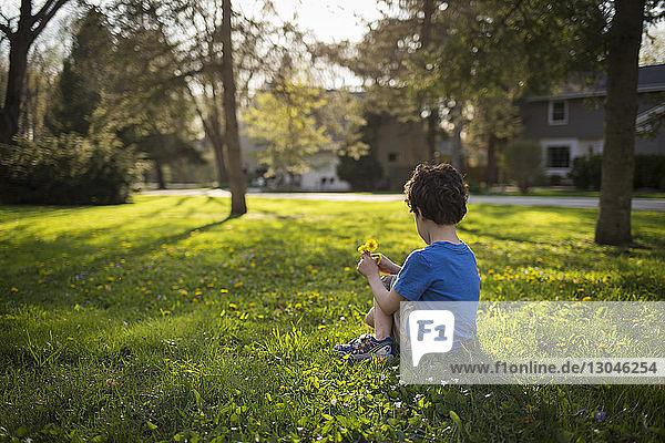 Junge hält Blumen  während er auf einem Grasfeld im Garten sitzt