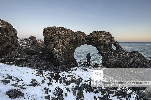 Rückansicht eines Wanderers  der im Winter am natürlichen Bogen am Strand steht