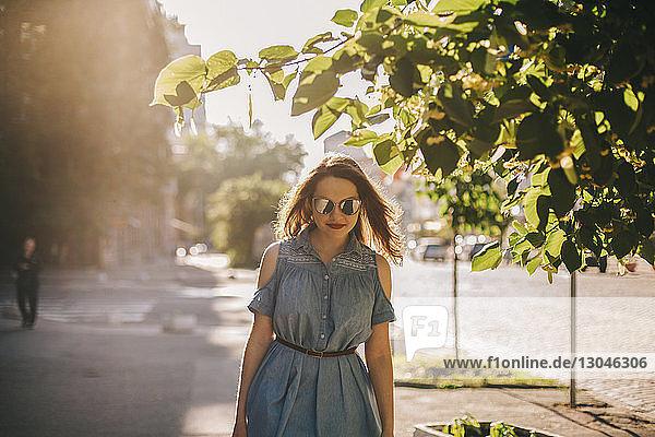 Junge Frau mit Sonnenbrille geht bei Sonnenschein in der Stadt auf dem Bürgersteig