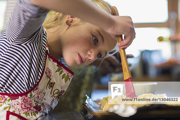 Girl applying oil on food with brush