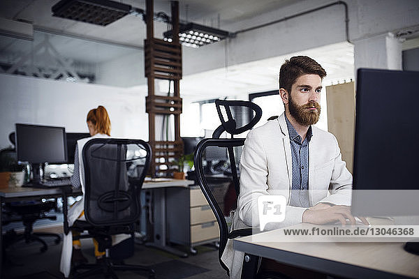 Geschäftsmann mit Desktop-Computer im Kreativbüro