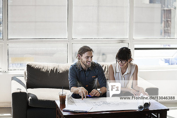 Business people looking at blueprint and discussing in creative office