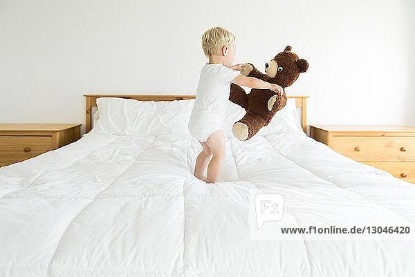 Süßer Junge spielt mit Teddybär  während er auf dem Bett steht