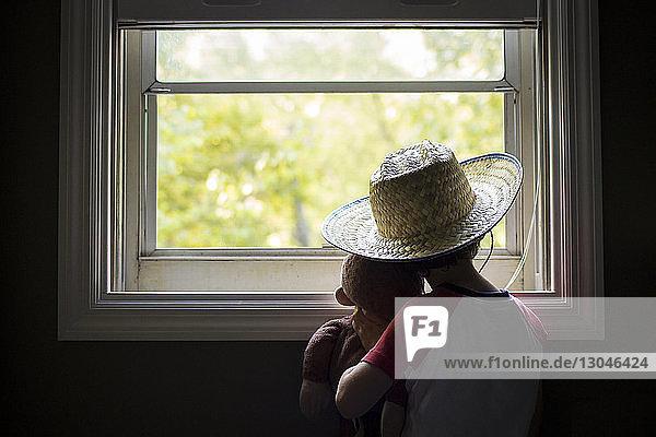 Rückansicht eines Jungen  der ein Stofftier hält  während er zu Hause durch ein Fenster schaut