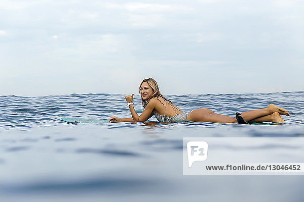 Portrait of smiling woman gesturing while surfing in sea against cloudy sky