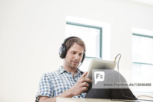 Geschäftsmann mit Tablet-Computer beim Musikhören im Büro Geschäftsmann mit Tablet-Computer beim Musikhören im Büro