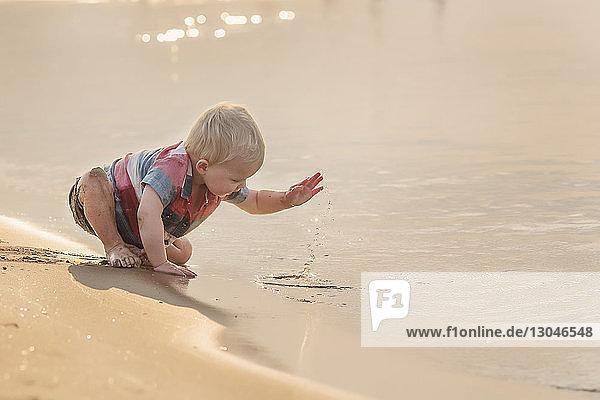Kleiner Junge spielt mit Wasser  während er bei Sonnenuntergang am Strand sitzt