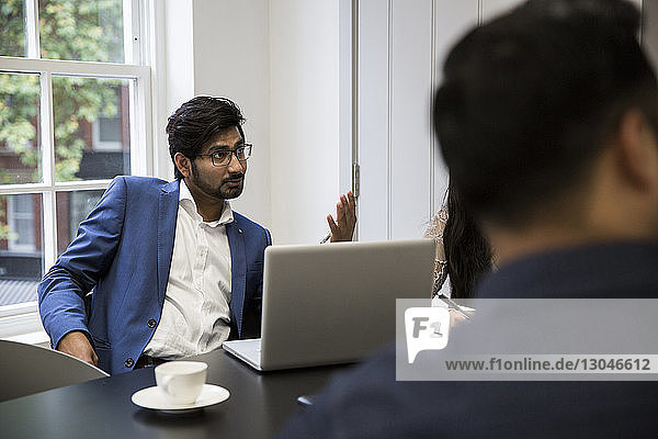 Business people during meeting at desk in office