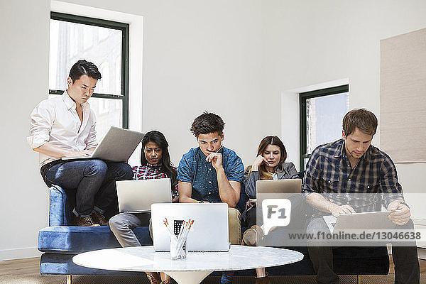 Geschäftsleute  die im Kreativbüro an Laptops arbeiten