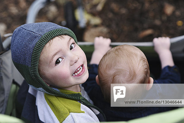 High angle portrait of boy sitting with brother in baby stroller at park